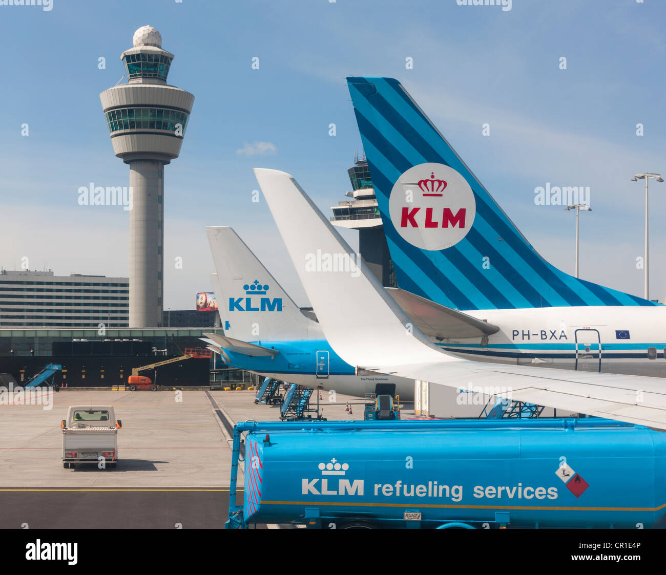 Amsterdam Schiphol Airport Air Traffic Control Tower with Royal KLM planes refueling at gate. Retro style colors - Stock Image