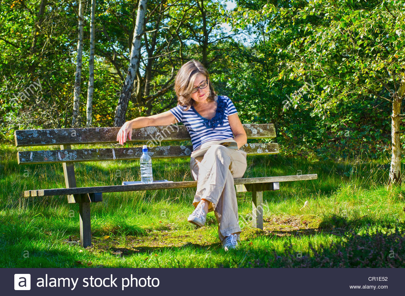 Older woman reading on park bench - Stock Image