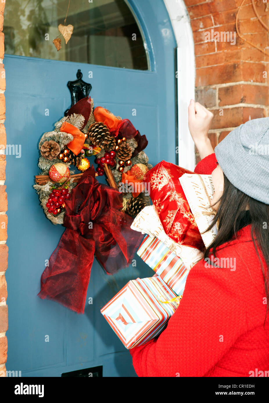 Woman with wrapped gifts at front door - Stock Image