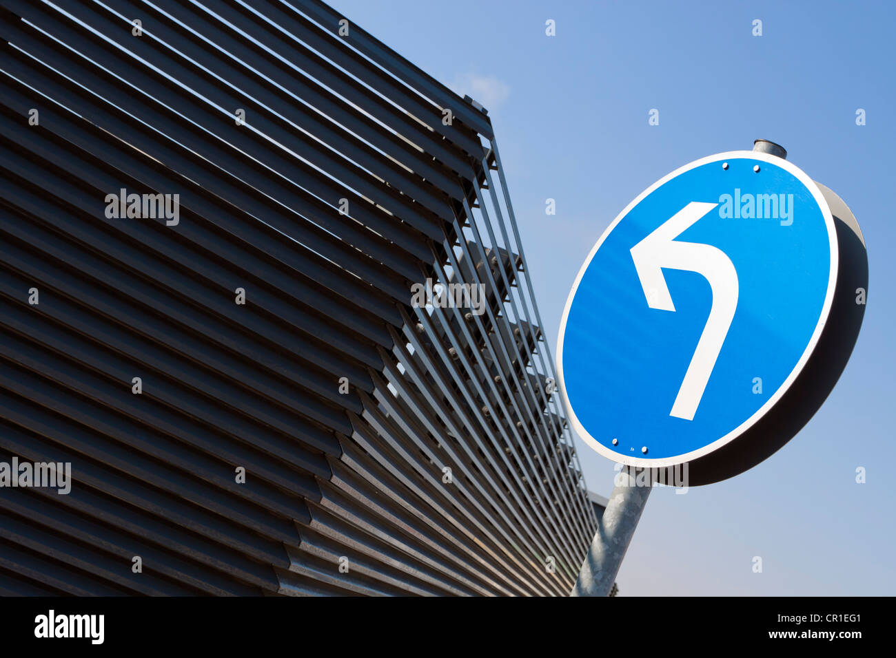 Turn arrow in front of a metal wall - Stock Image