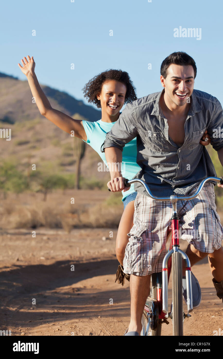 Couple riding bicycle on dirt road - Stock Image
