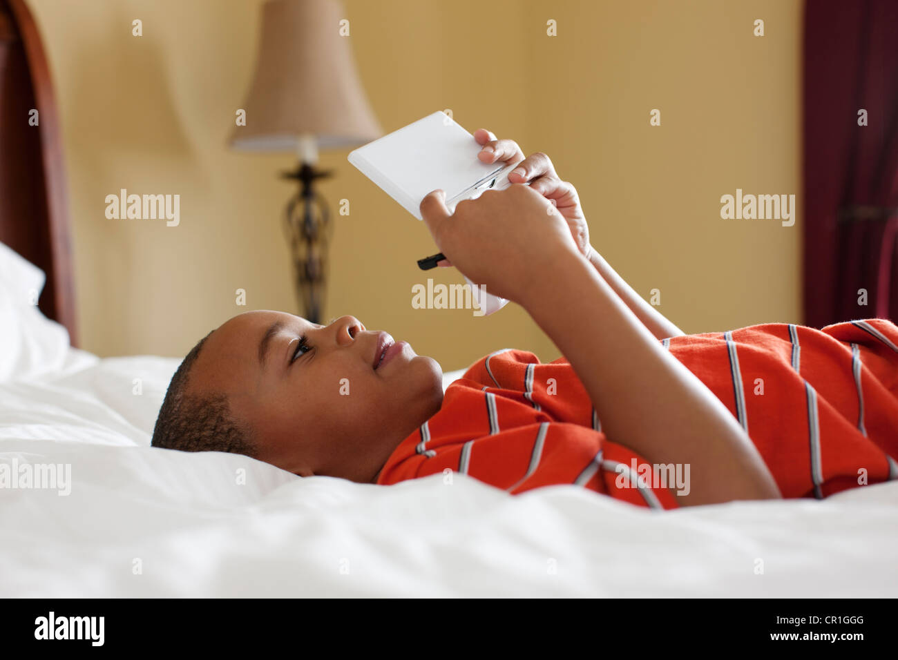 Boy playing handheld video game on bed Stock Photo