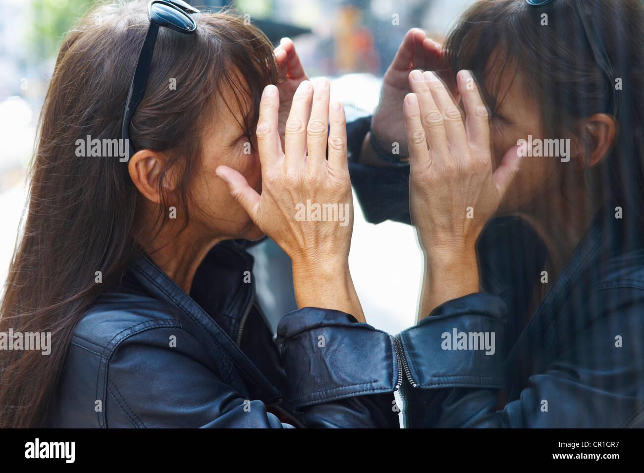 Woman peering through window - Stock Image