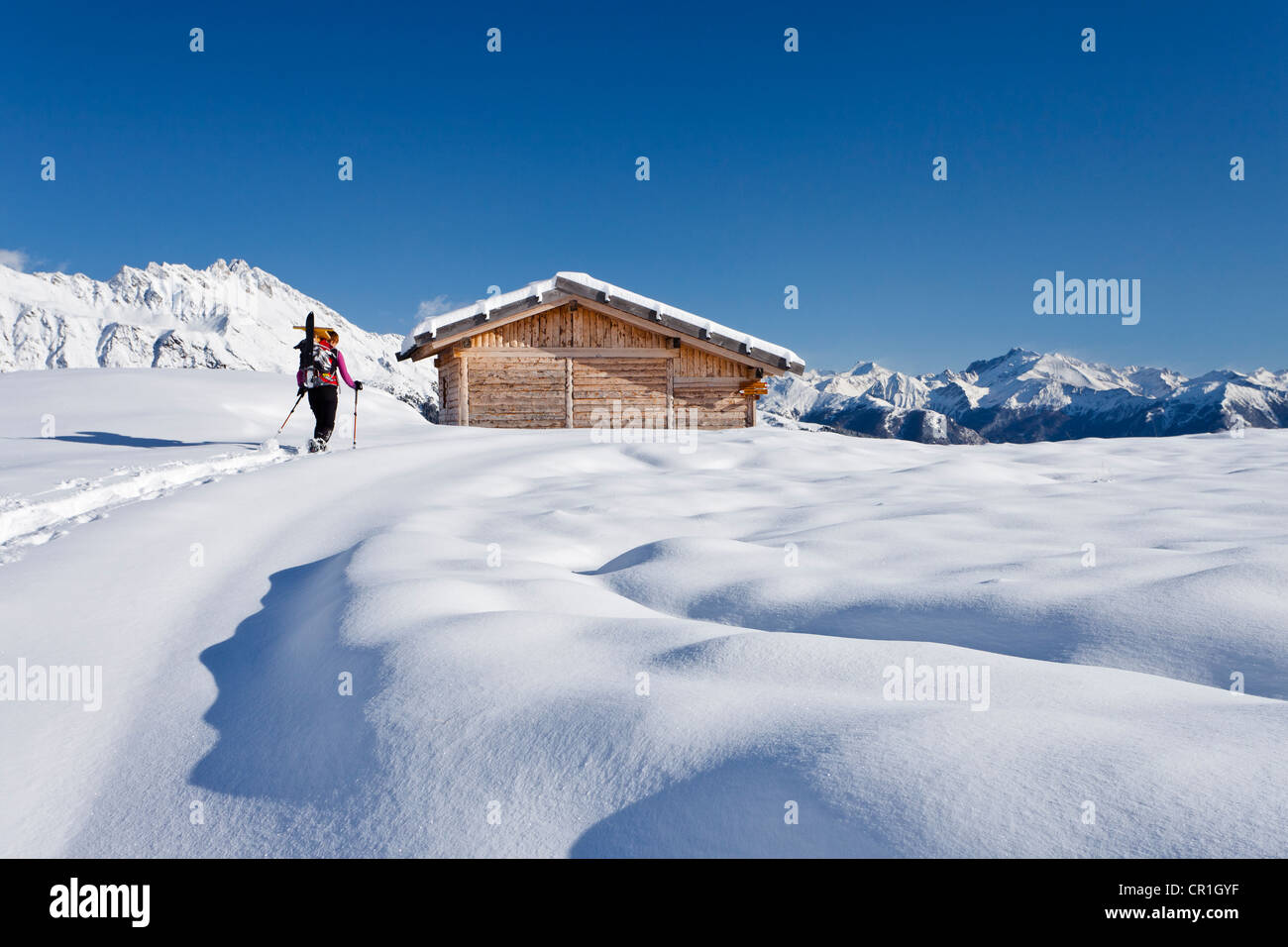 Snowshoer ascending to Jagelealm alpine pasture in Ridnauntal Valley above Entholz, looking towards Rosskopf Mountain - Stock Image