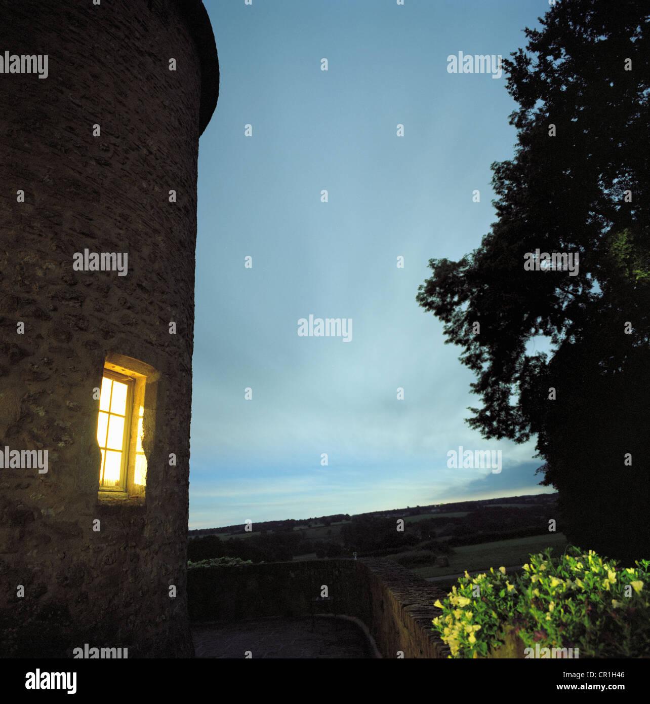 Lit window of stone house - Stock Image