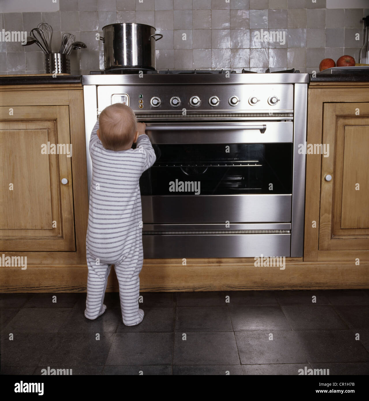 Infant standing by oven in kitchen Stock Photo