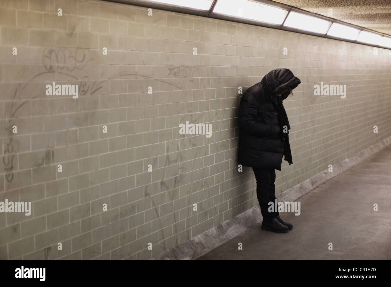Hooded person leaning on subway wall - Stock Image