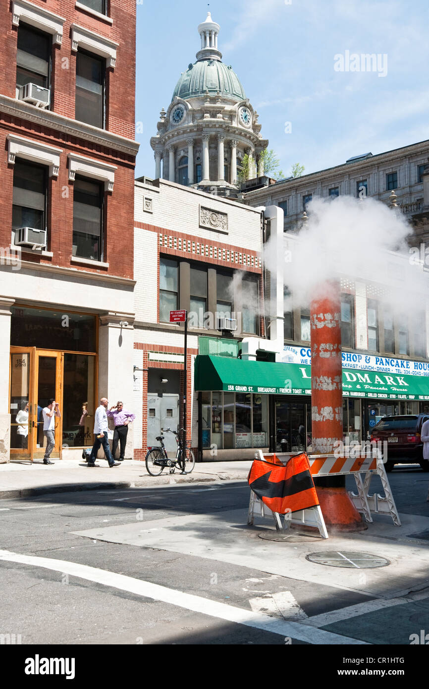 New York street scene Grand street with ubiquitous steam pipe vent & view of copper dome landmarked former Police - Stock Image