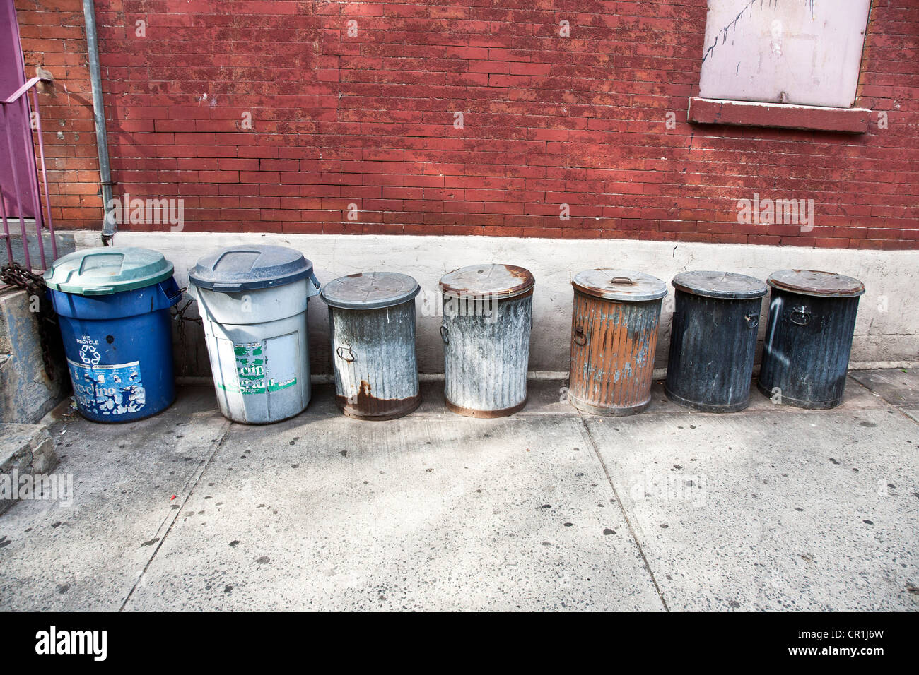 row of old fashioned galvanized garbage cans with traces of paint lined up against a brick wall Hells Kitchen neighborhood - Stock Image