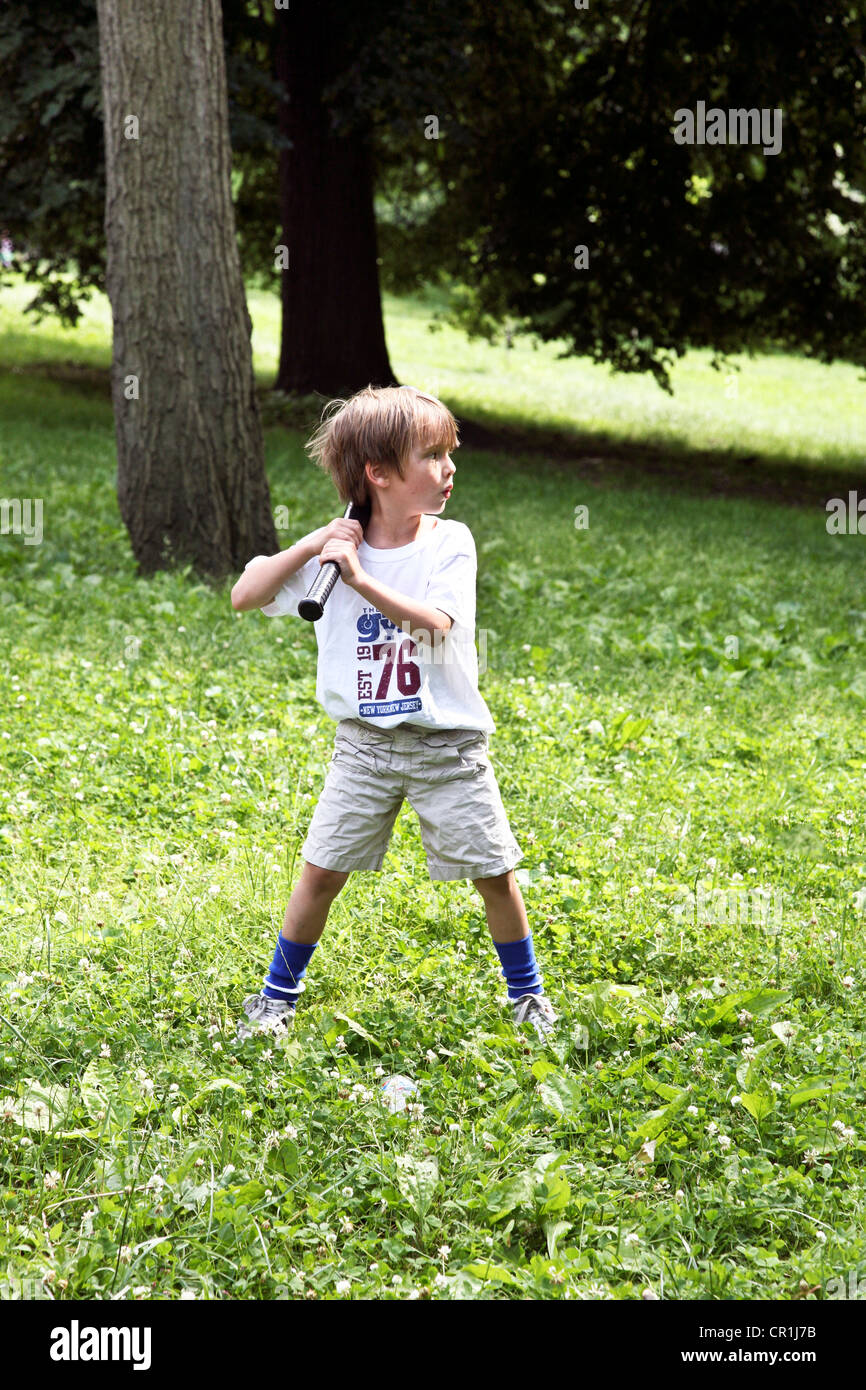 small boy with large baseball bat fully prepared for the pitch from his dad on a grassy area in Riverside Park New - Stock Image