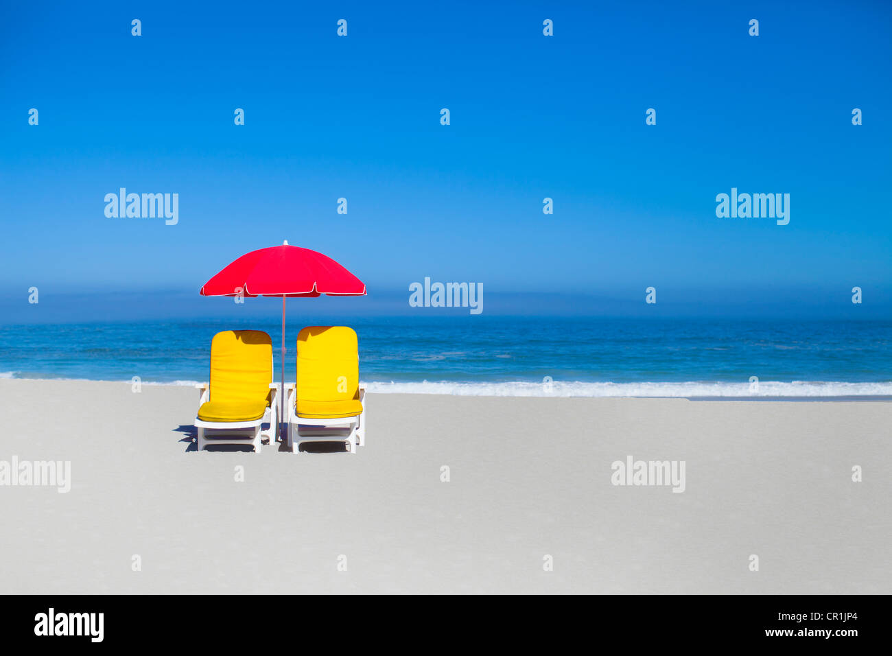 Empty lawn chairs and umbrella on beach - Stock Image