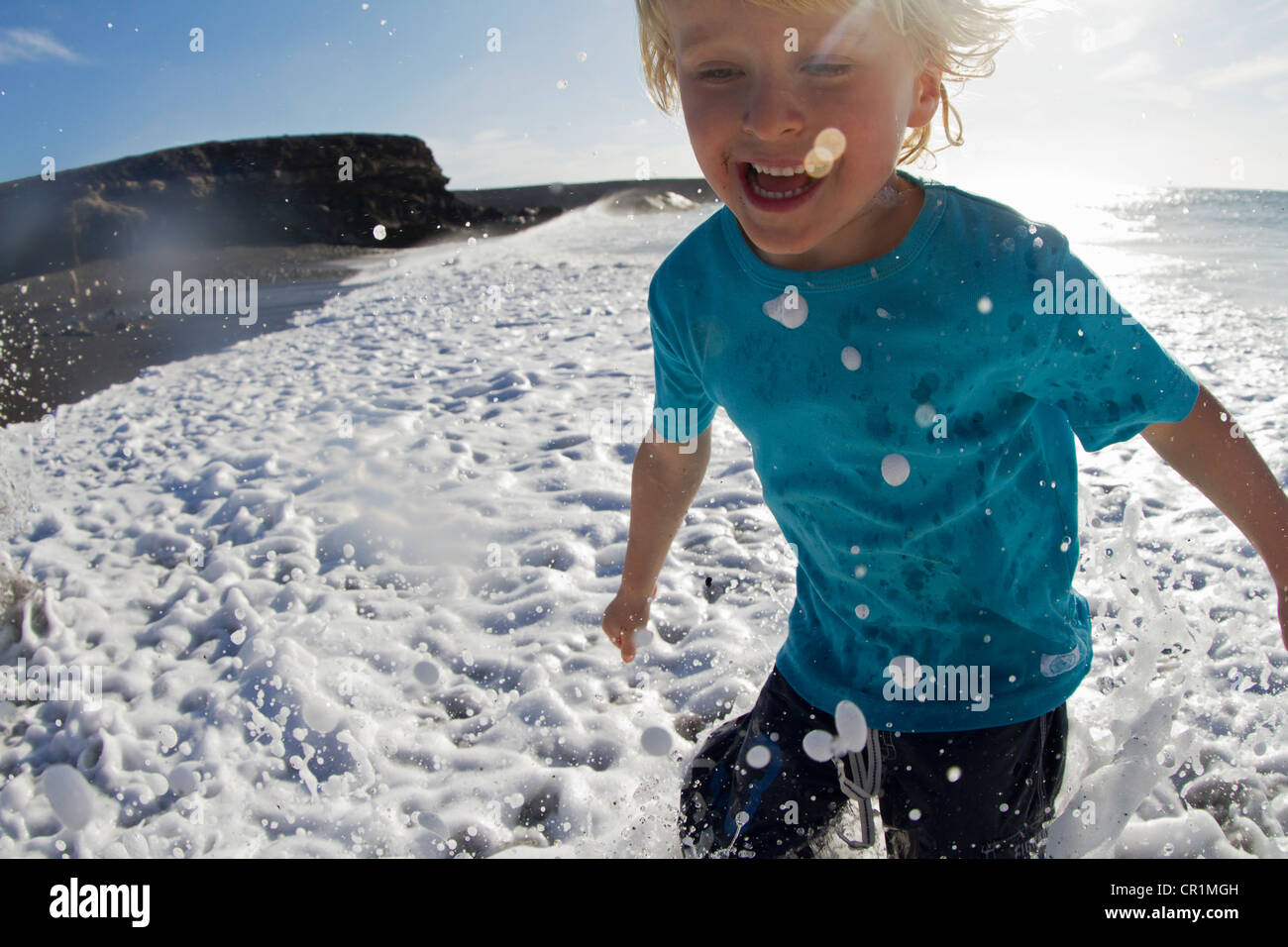 Boy playing in waves on beach - Stock Image