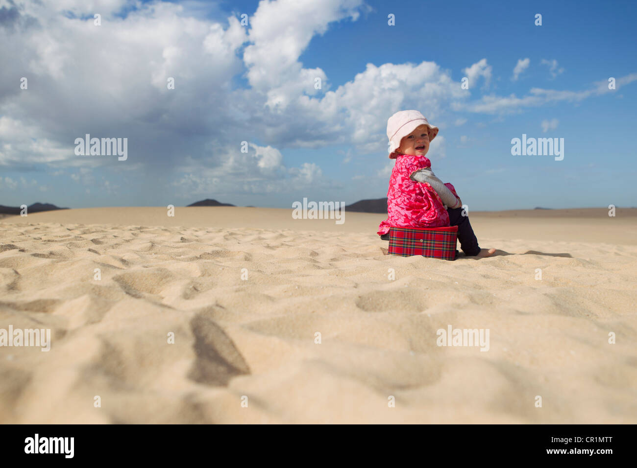 Toddler sitting on suitcase on beach - Stock Image