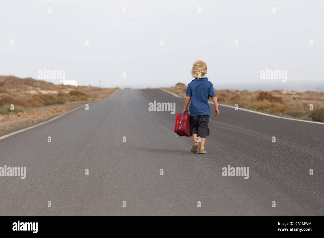 Boy carrying suitcase on rural road - Stock Image