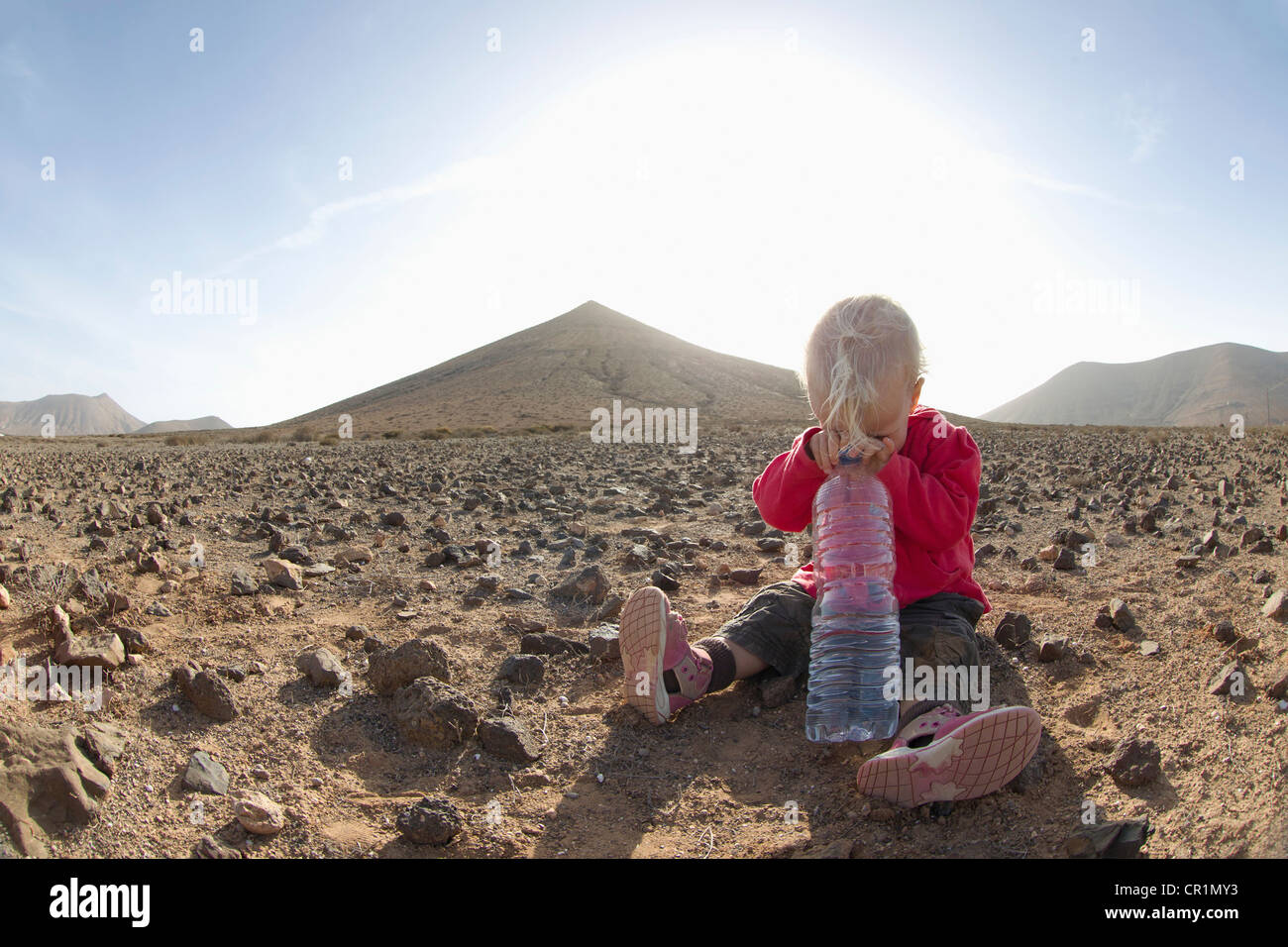 Toddler with bottle of water in desert - Stock Image