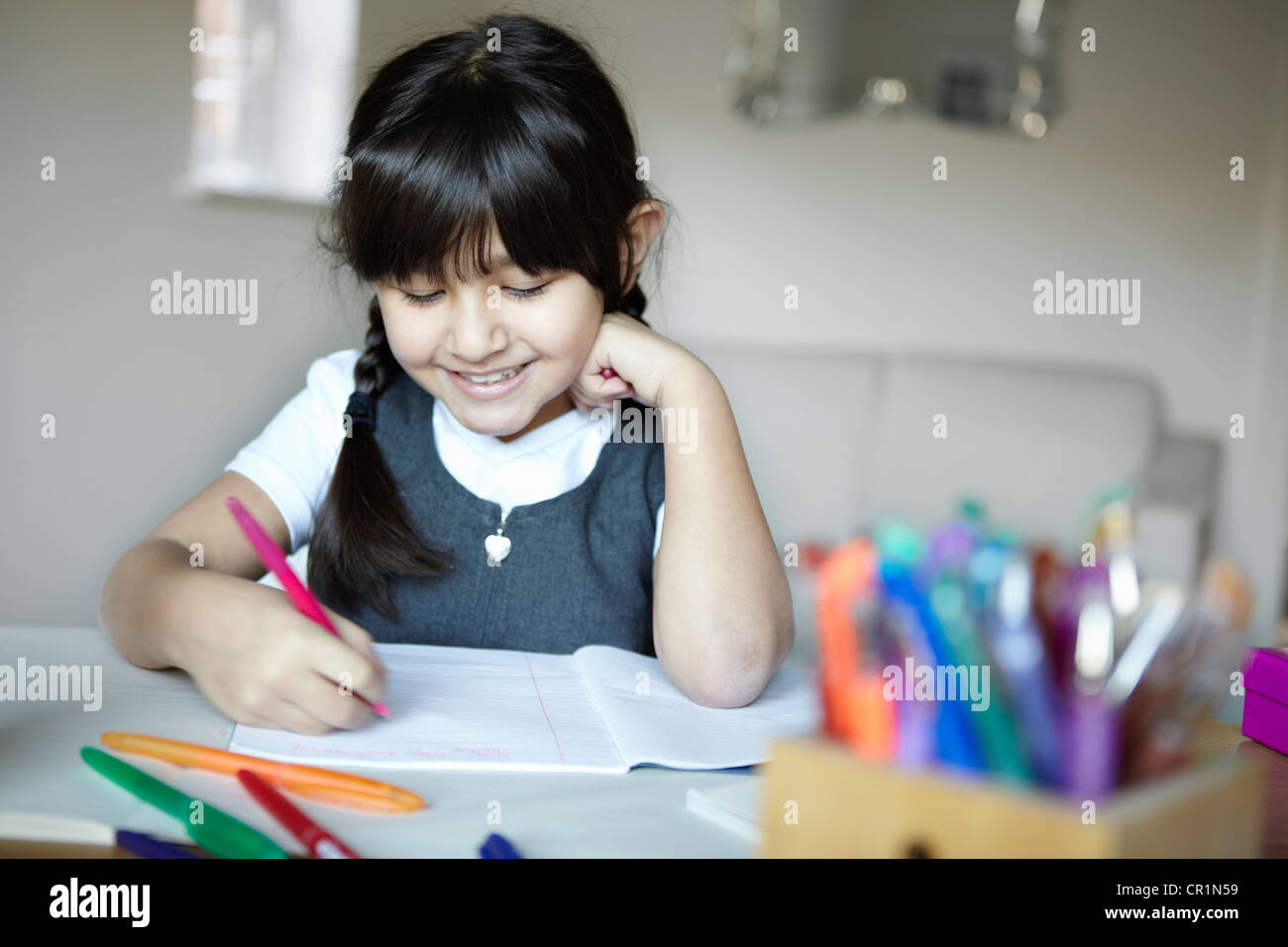 Schoolgirl writing at desk - Stock Image