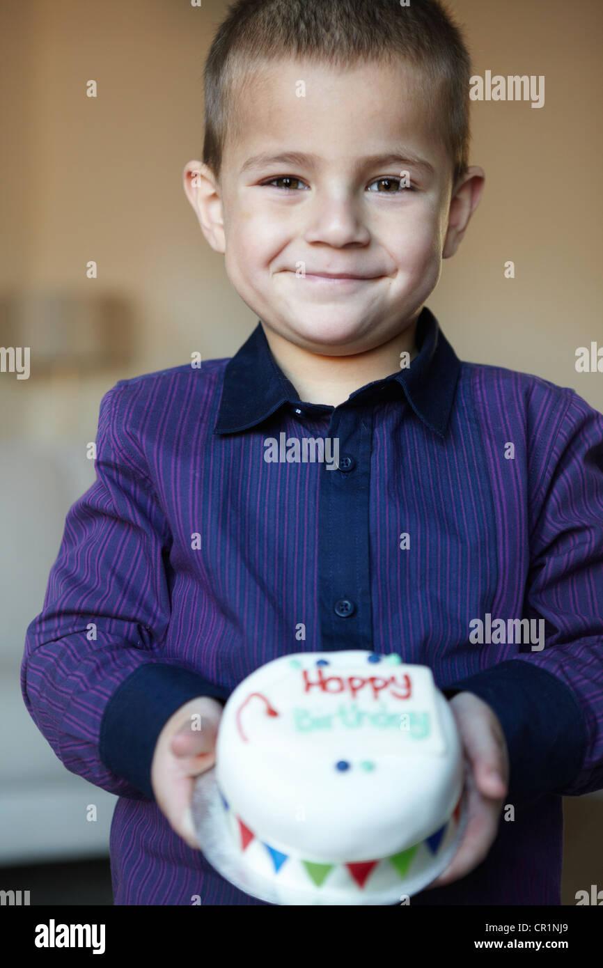 Boy holding miniature cake - Stock Image
