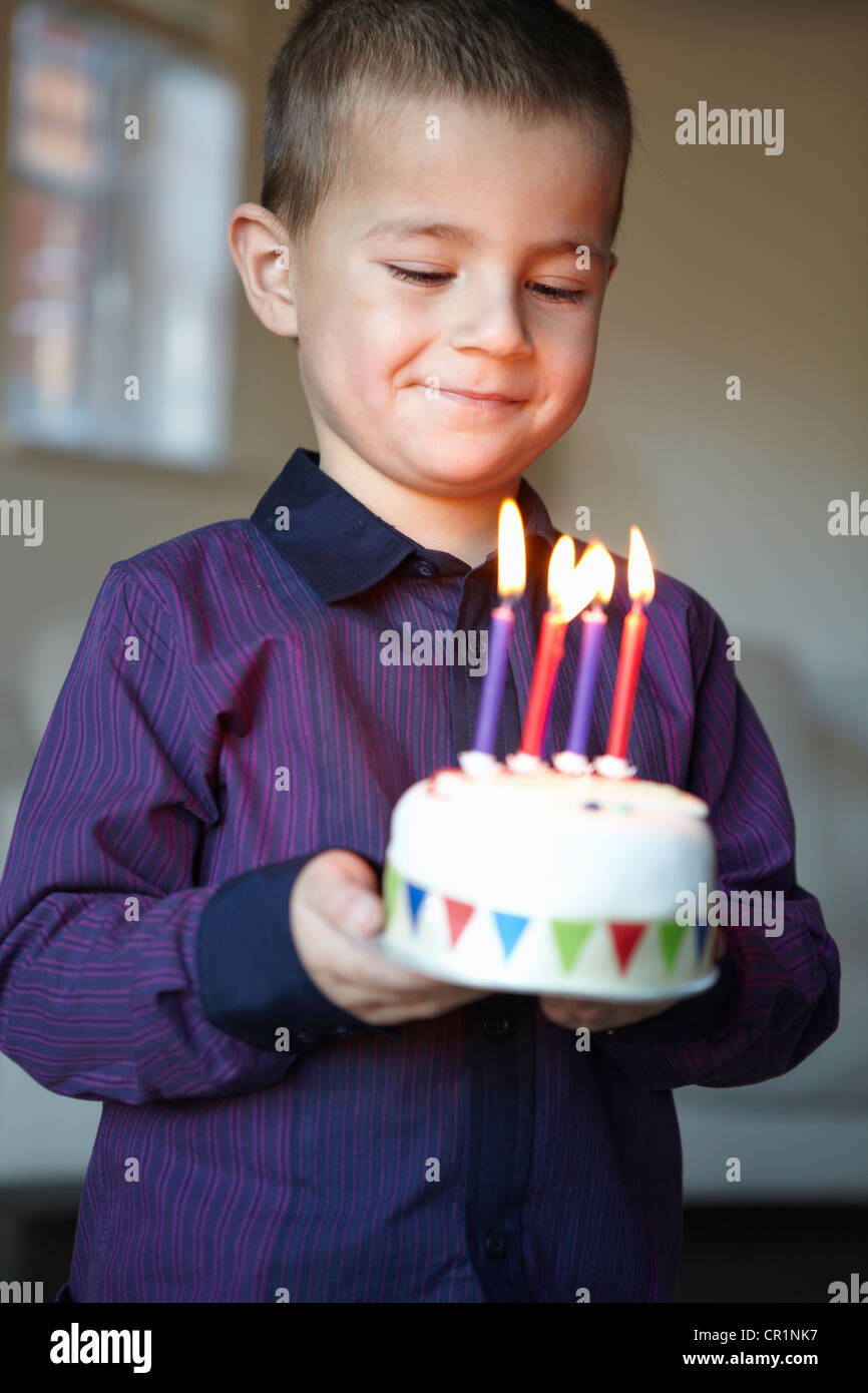 Boy holding miniature cake with candles - Stock Image