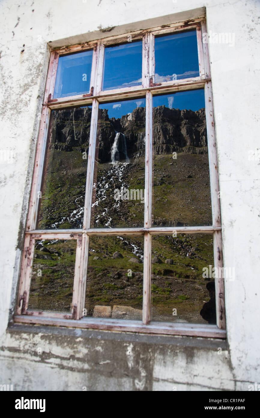 Rural waterfall reflected in window - Stock Image