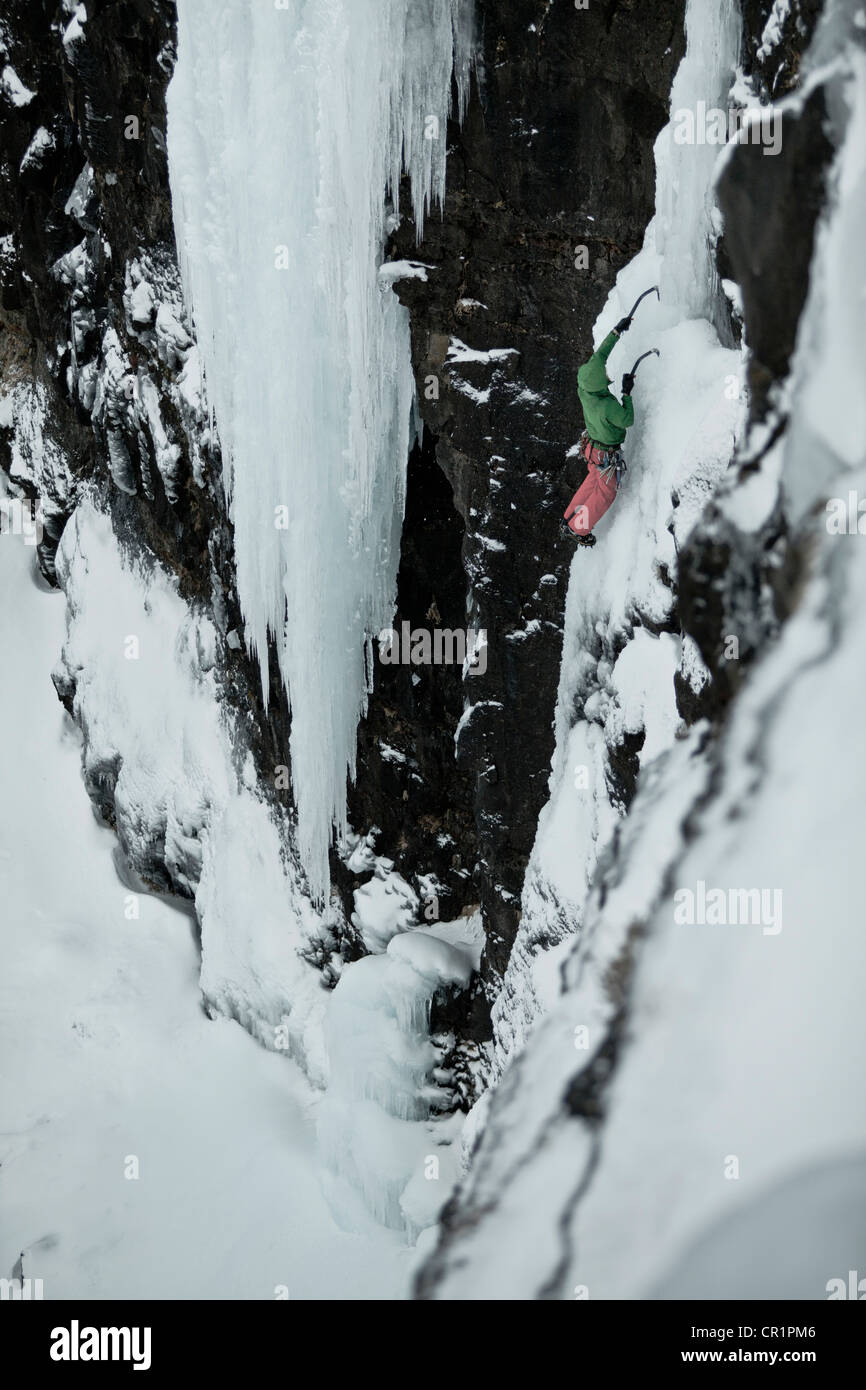 Climber with picks descending snowy hill - Stock Image
