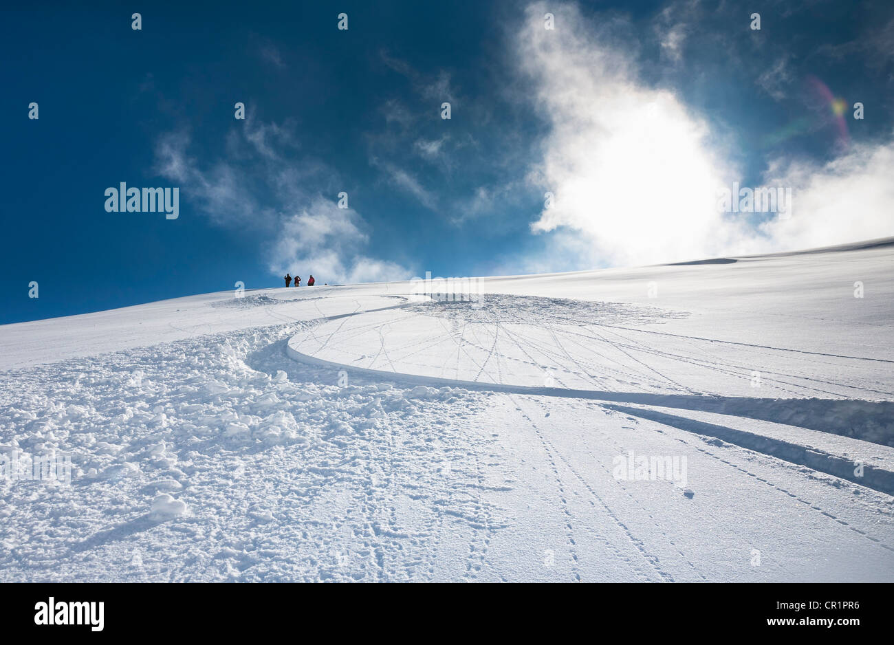 Ski and snowboard tracks on snowy hill - Stock Image