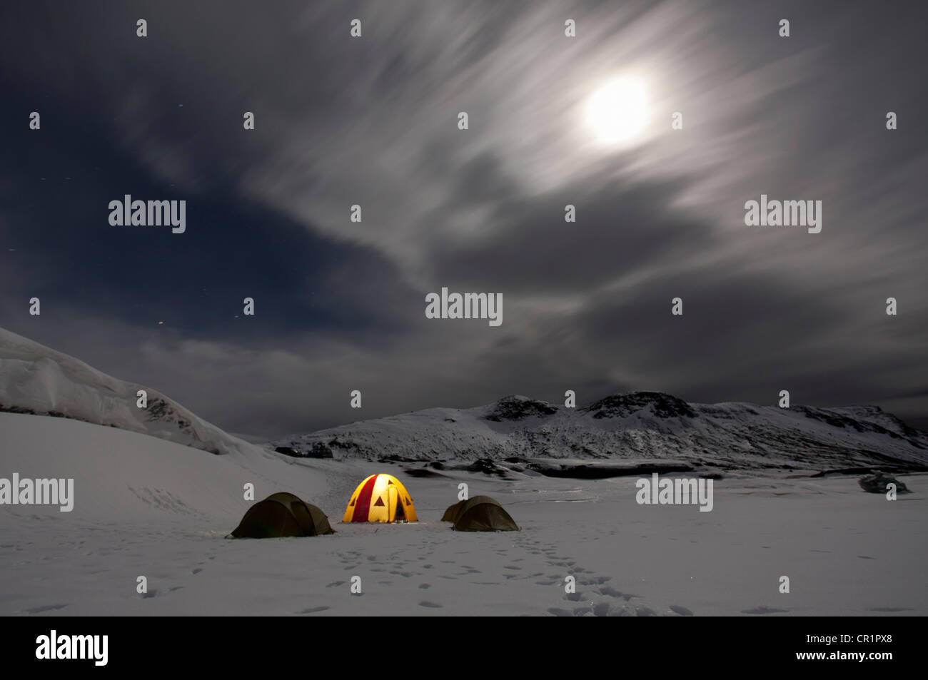 Illuminated tent at glacier campsite - Stock Image