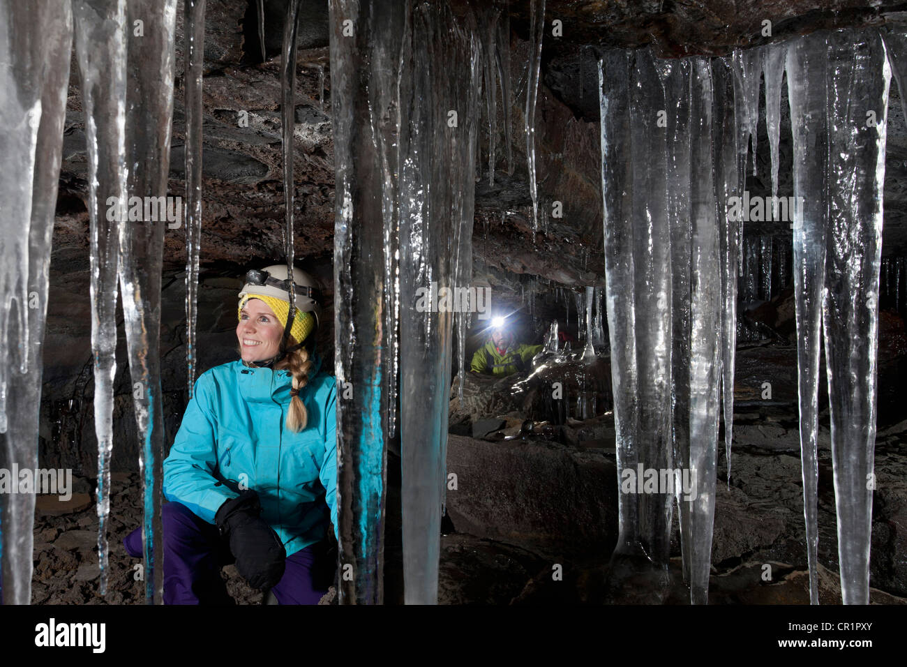 Hiker admiring icicles in cave - Stock Image