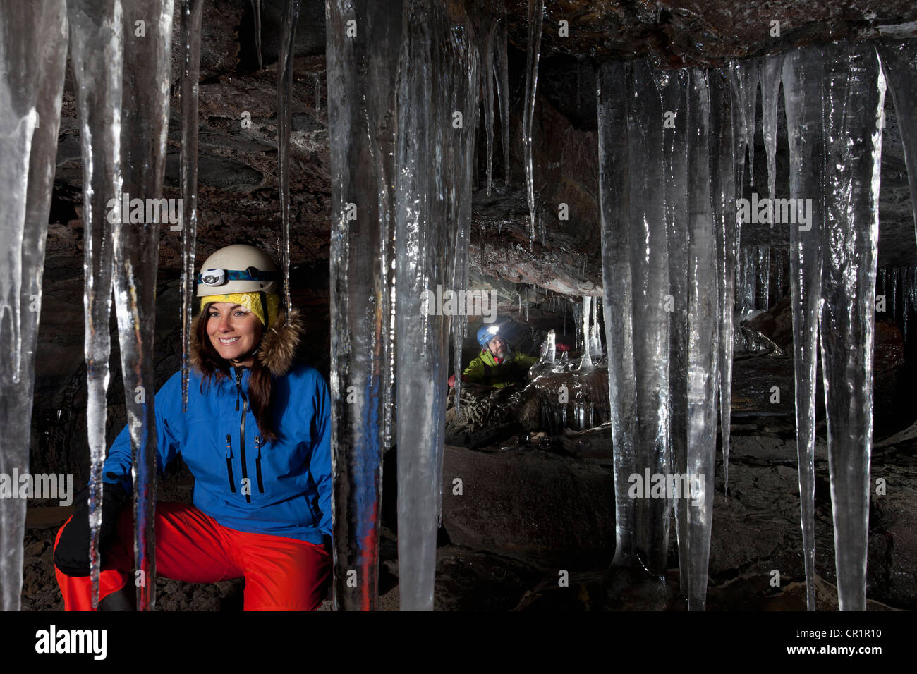 Hiker with icicles in glacial cave - Stock Image