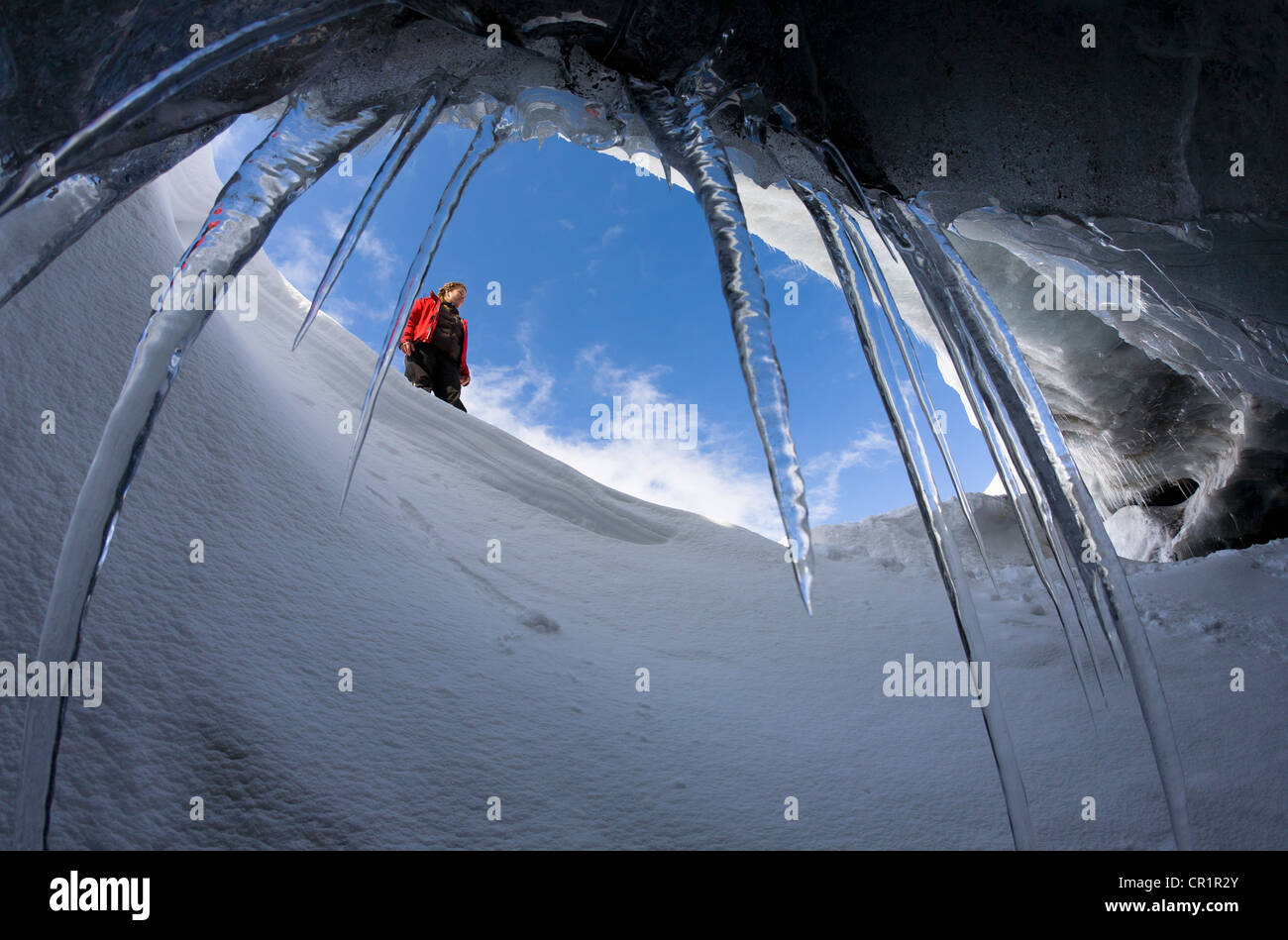 Hiker viewed from glacial cave - Stock Image