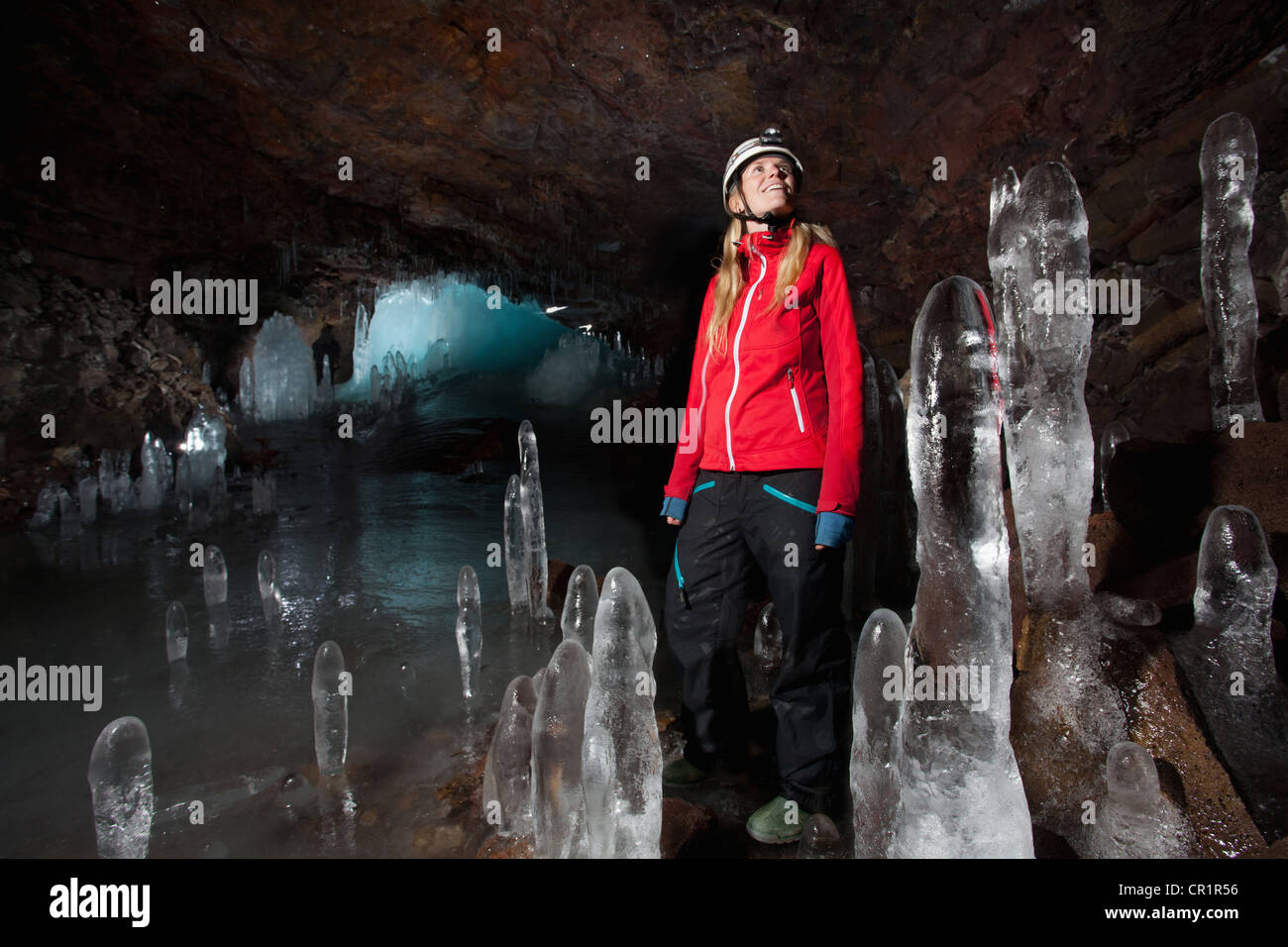 Hiker with stalactites in glacial cave - Stock Image