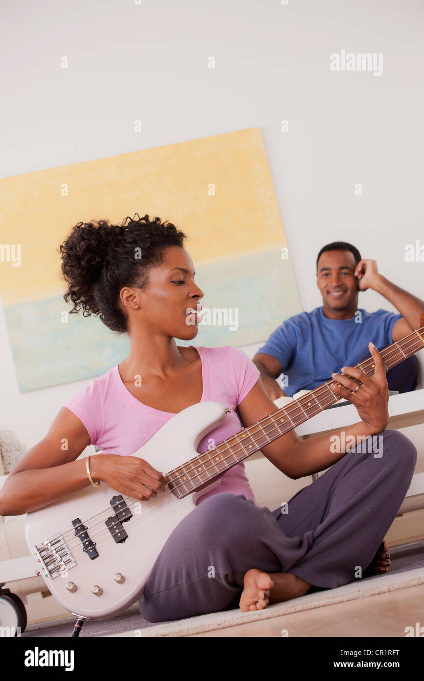 USA, California, Los Angeles, Woman playing electric guitar, man in background Stock Photo