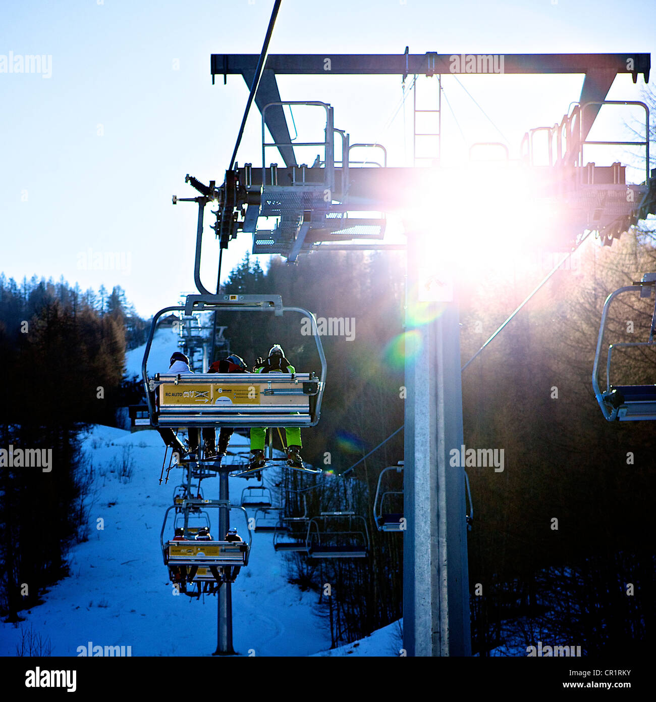 skiers on chair lift with sun glare - Stock Image