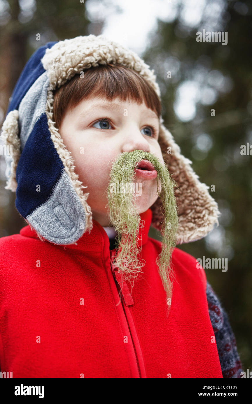 Boy playing with moss outdoors - Stock Image