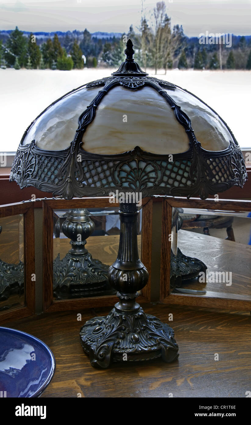 antique decorative metal lamp is the focal point in this still life. Surround by mirrors and other vintage objects Stock Photo