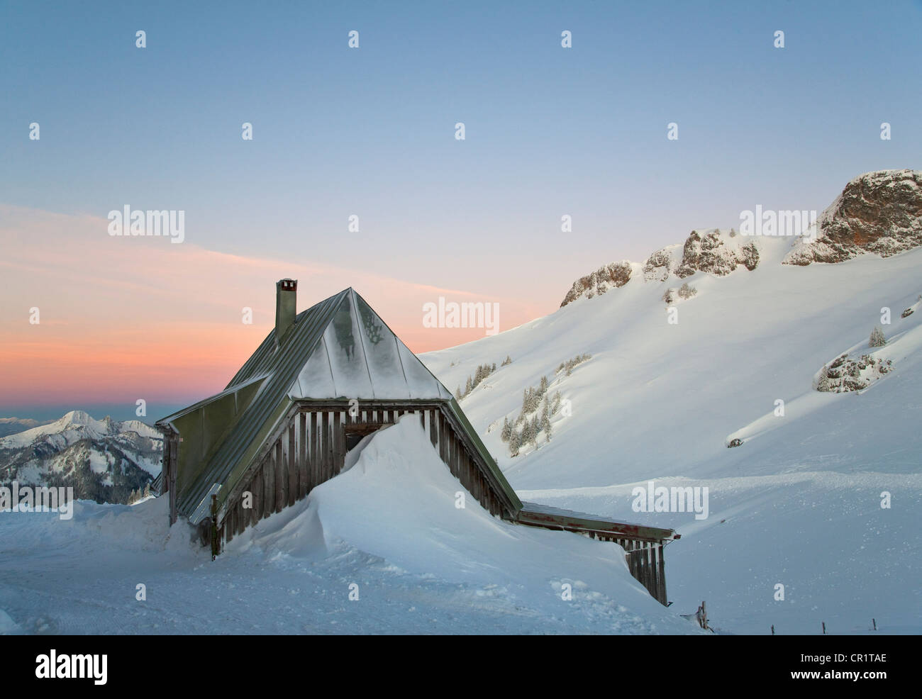 Snow piled up by house on hillside Stock Photo