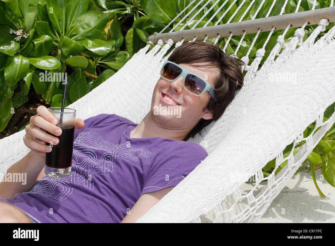 Young man relaxing in a hammock, holding a drink, Maldives, Indian Ocean - Stock Image