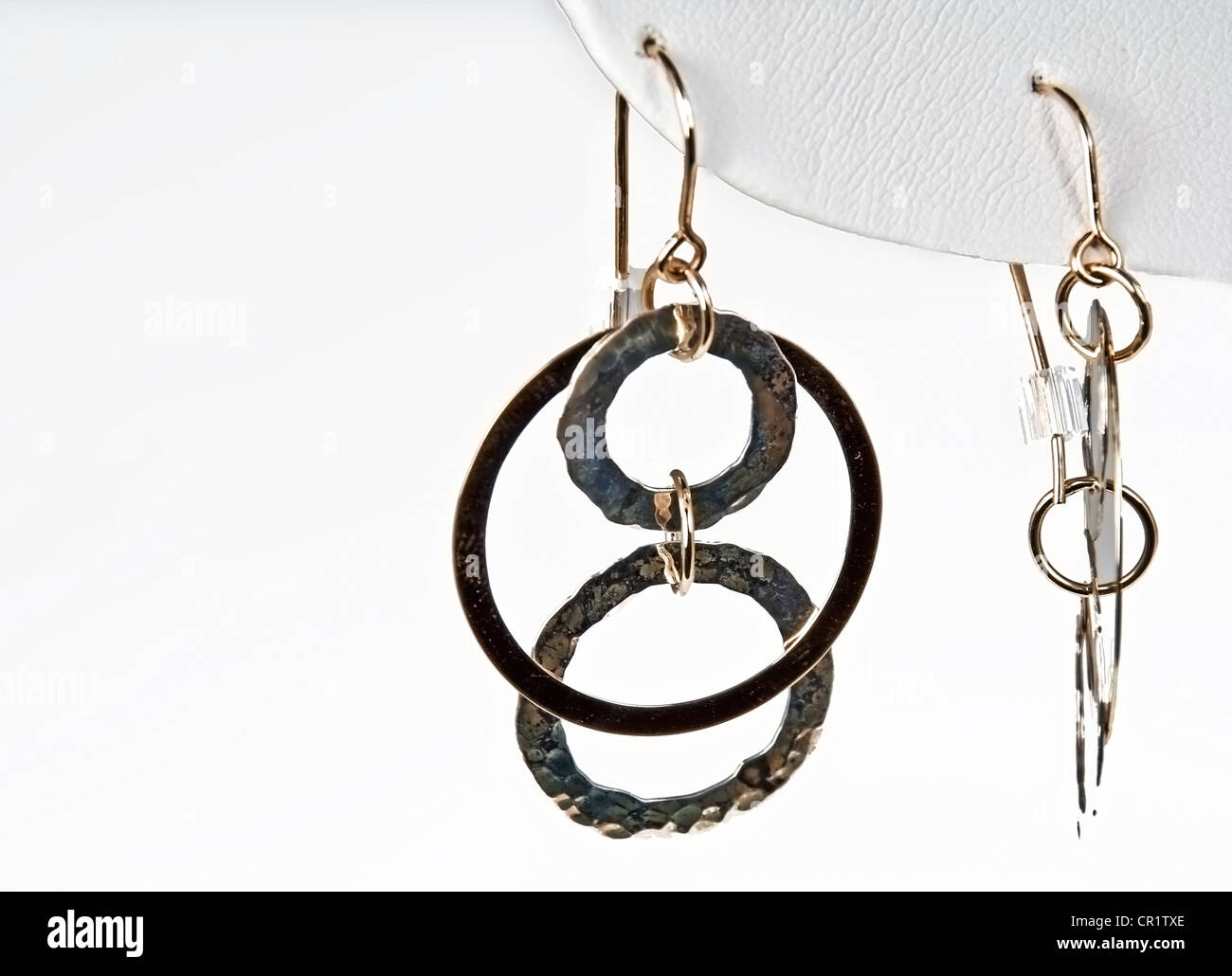 pair of gold round dangle earrings is jewelry shot macro on a white background and horizontal orientation. - Stock Image