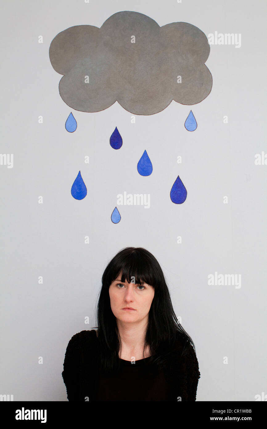 Woman standing under painted rain cloud - Stock Image