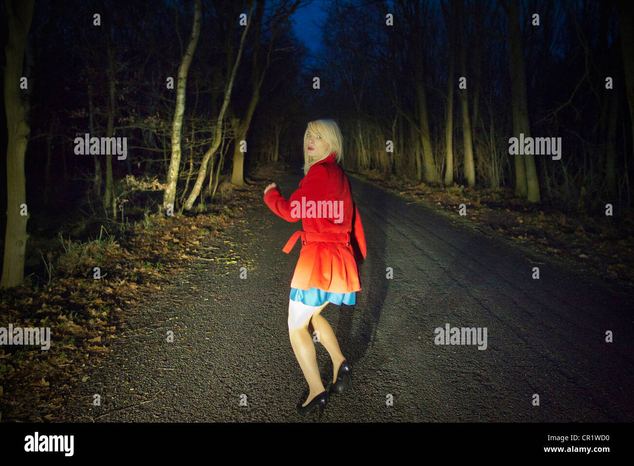 Woman running in fear in woods at night - Stock Image