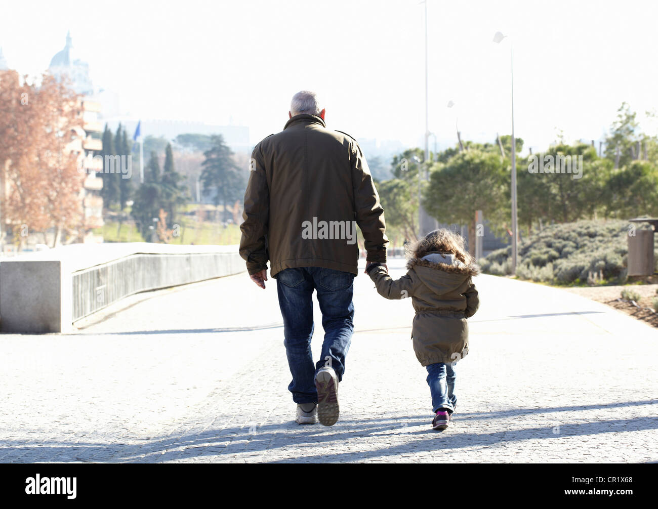 Father and daughter walking in park - Stock Image