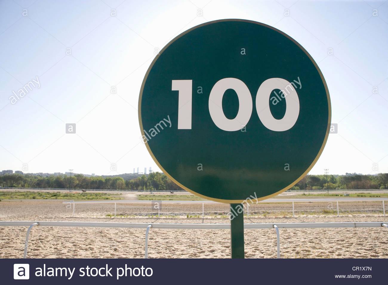Sign reading ì100î on sandy track - Stock Image