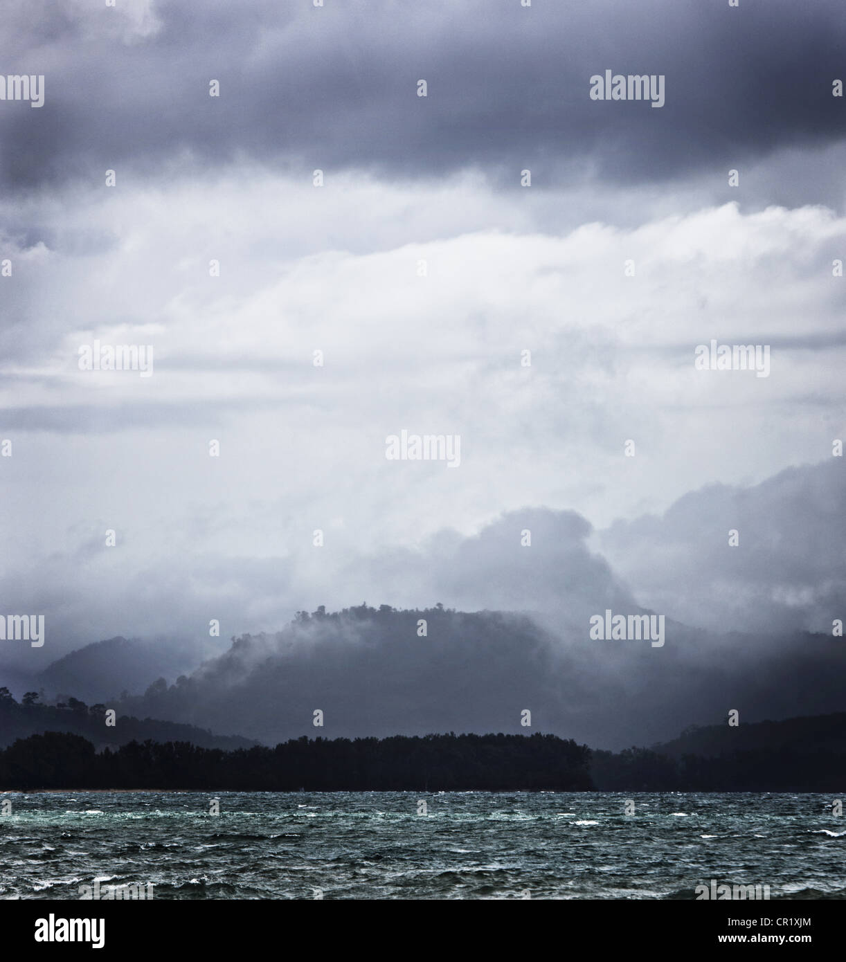 Clouds over rocky lake Stock Photo