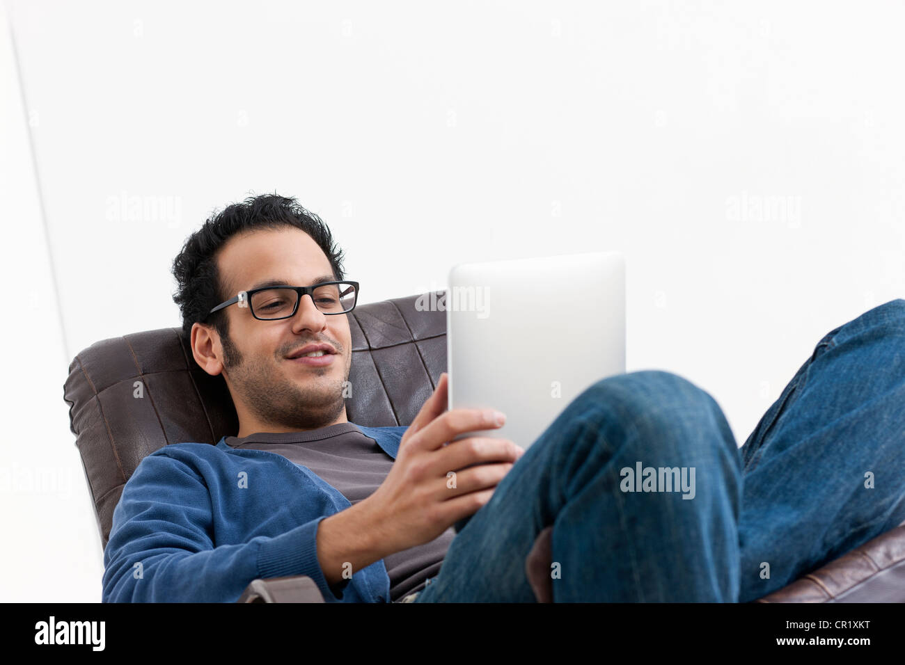 Smiling man using tablet computer - Stock Image