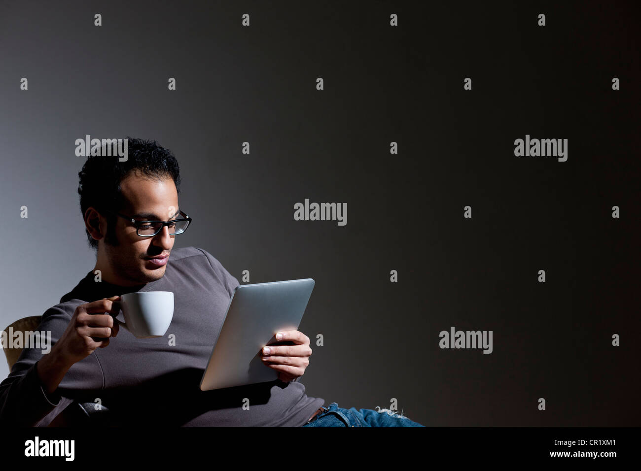 Man with coffee using tablet computer - Stock Image