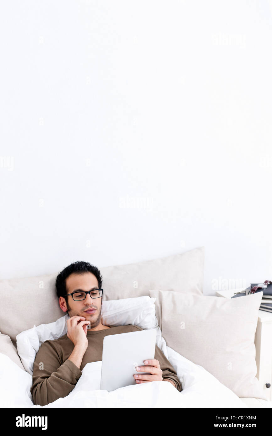 Man using tablet computer in bed - Stock Image