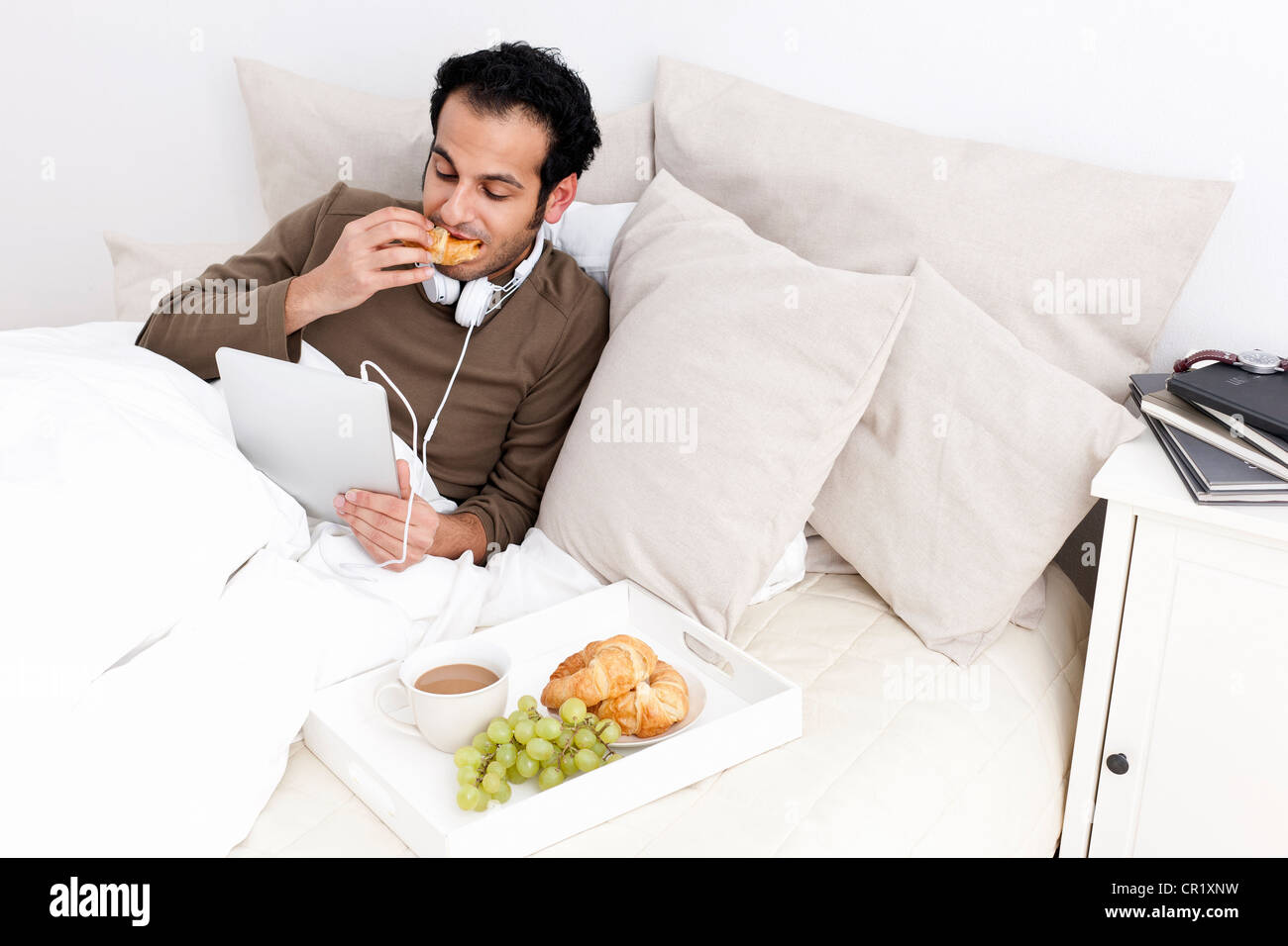 Man with tablet computer eating in bed - Stock Image