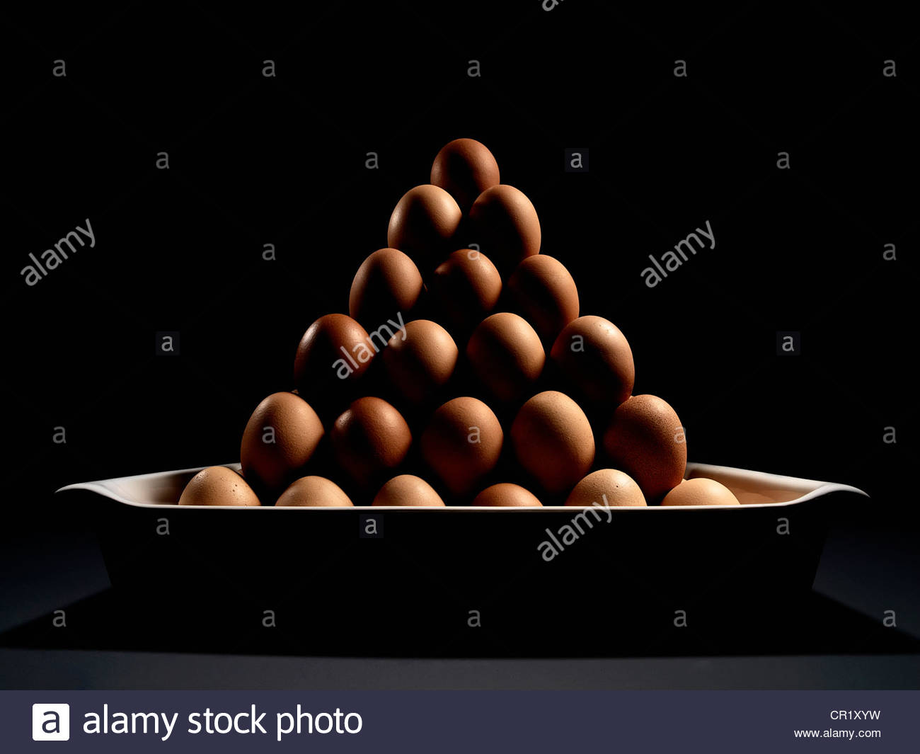 Eggs stacked in dish - Stock Image