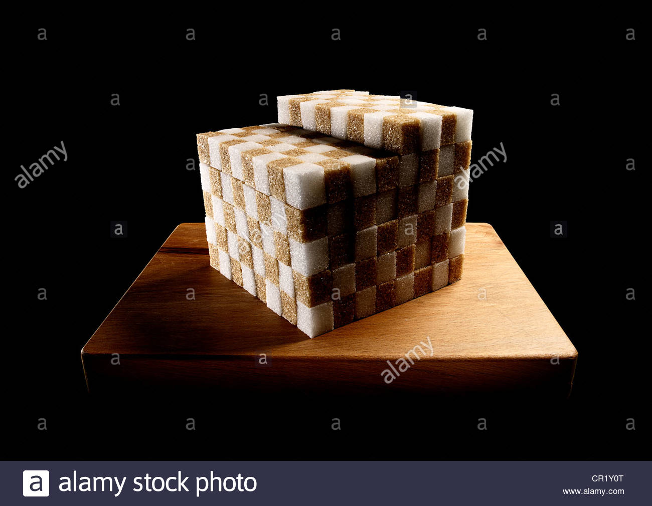 Sugar cubes stacked neatly on board - Stock Image