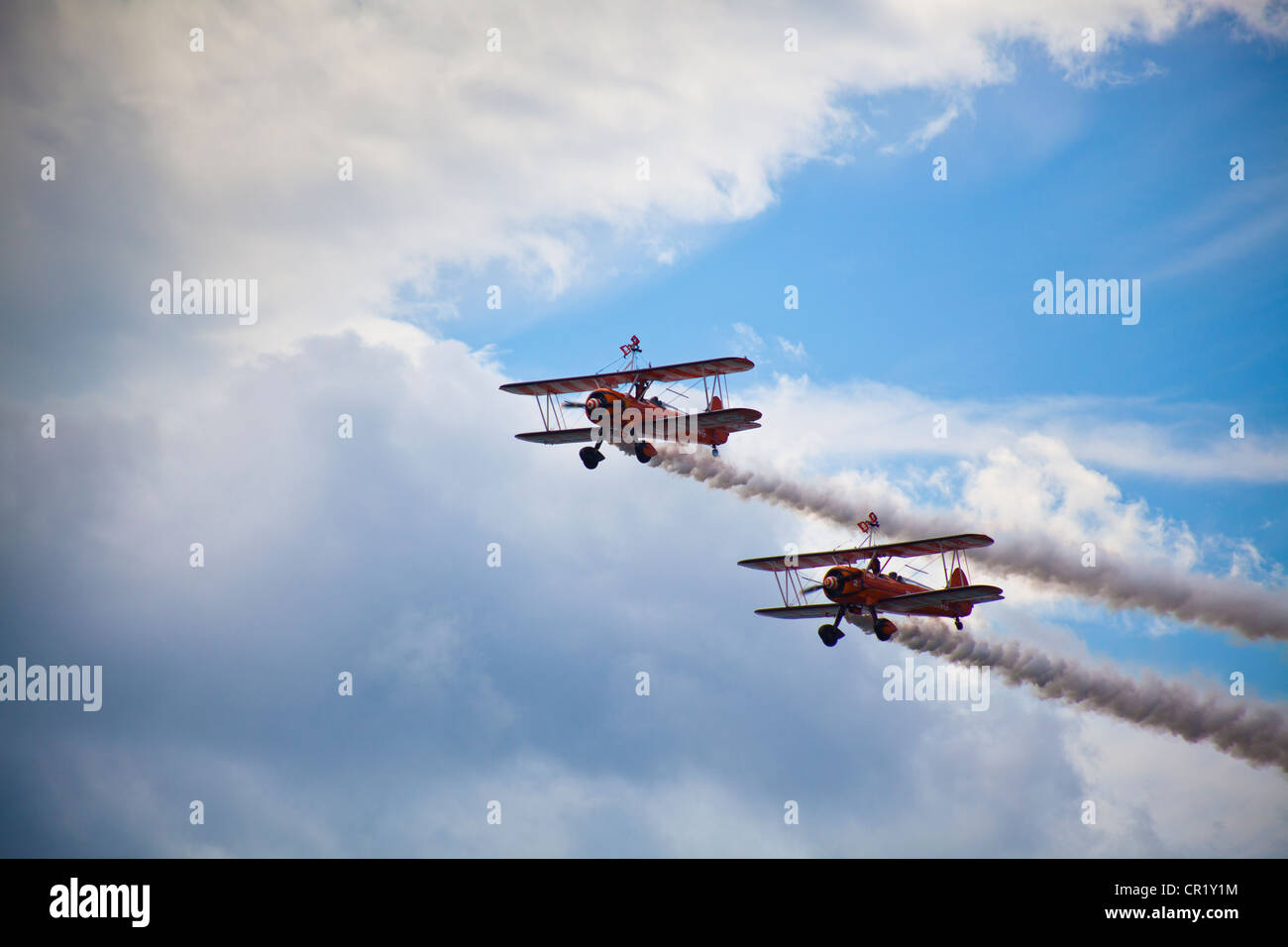 2 Breitling propeller Bi-Planes fly past in formation at Bournemouth Air show with wing walkers climbing into position - Stock Image