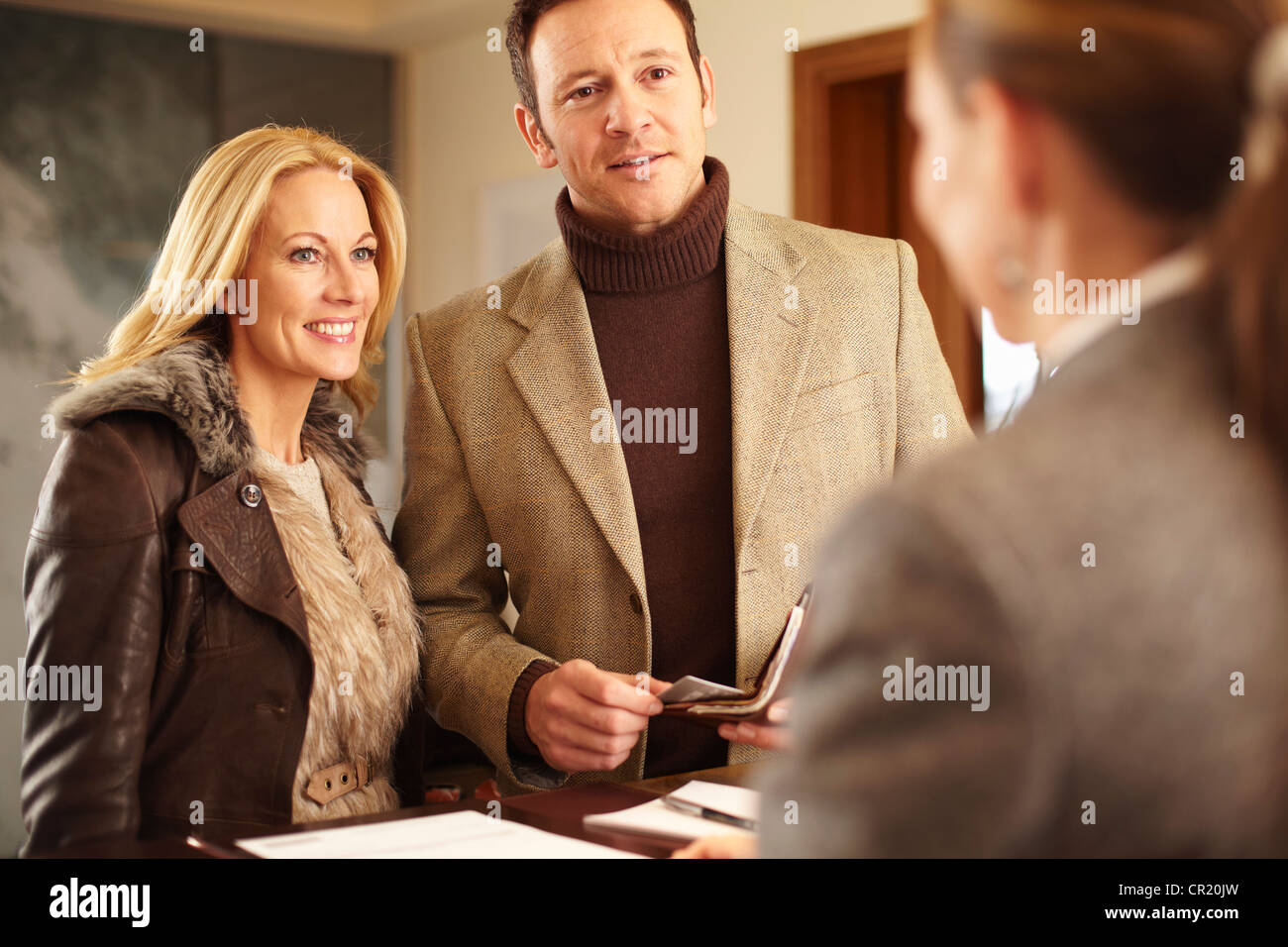 Couple checking in to hotel - Stock Image